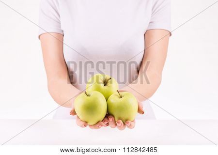 Woman demonstrating three green apples.