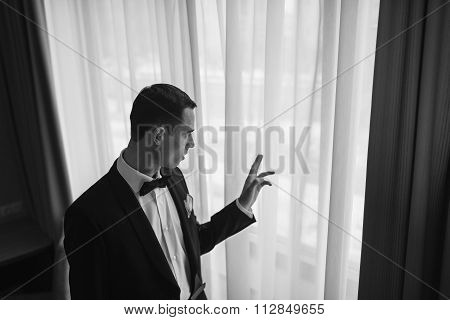 A Man In A Tuxedo Looking Out The Window.