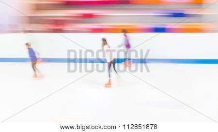 Blur motion image of people ice skating in the ice rink indoors.
