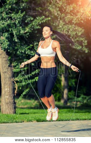 fitness and lifestyle concept - woman doing sports outdoors. girl with skipping rope