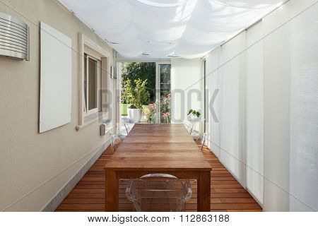 Architecture; veranda with white curtains and wooden table