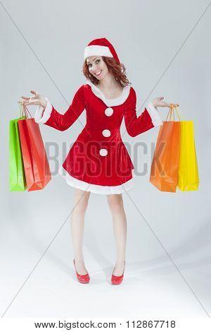 Female Santa Helper with Plenty of Shopping Bags Against White