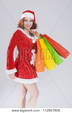 New Year Concept. Happy Looking Young Caucasian Red Haired Female in Santa Hat With Shopping Bags