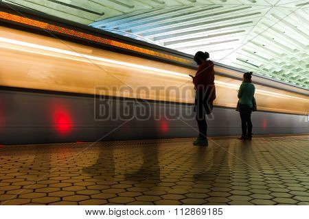 Washington DC Metro station with train and passengers are in motion blur