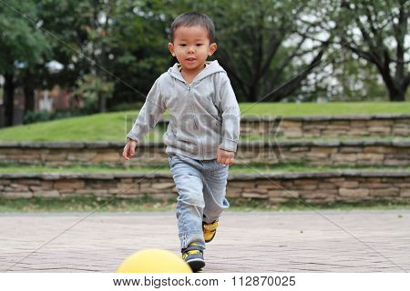 Japanese boy kicking a yellow ball (3 years old)