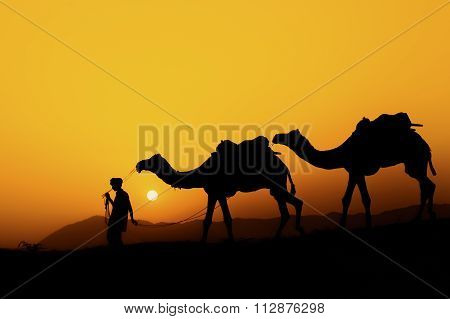 Silhouette of the Camel Trader across the sand dune.