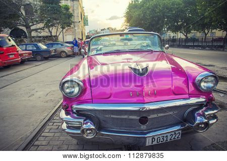 HAVANA, CUBA - 4 DEC, 2015. Pink vintage classic American car, commonly used as private taxi parked in Havana street.