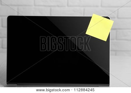 Empty yellow adhesive paper on laptop, on light background