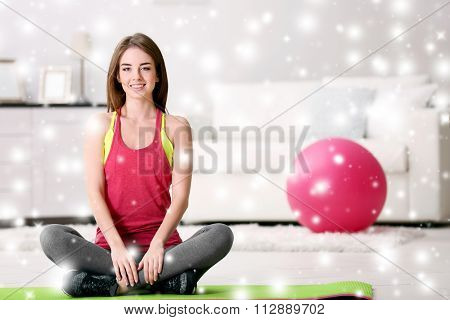 Beautiful young girl with fit ball at home over snow effect