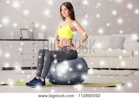 Beautiful young girl doing exercises with fit ball at home over snow effect