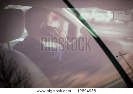 Handsome young man calling on his cellphone while at the wheel of his car