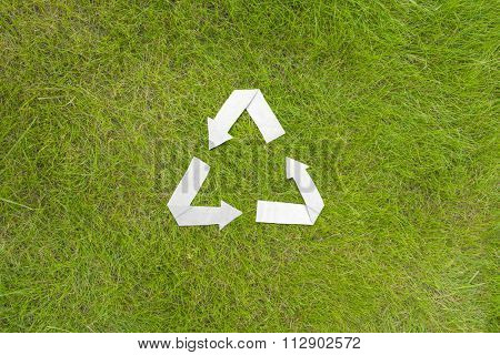 Paper recycle symbol on green grass background