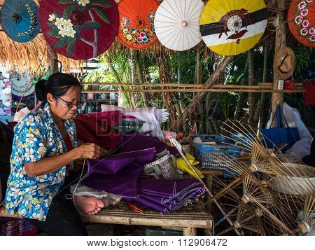 CHIANG MAI, THAILAND - NOVEMBER 22, 2015: An unidentified woman works on an umbrella in parasol factory in Chiang Mai, Thailand. This is a traditional craft that attracts local and foreign visitors.