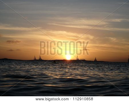 Dramatic Sunset On Waters Of Waikiki Over The Ocean With Sail Boats On The Horizon