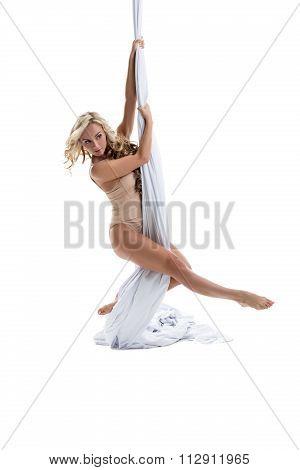 Playful girl posing while dancing on aerial silks