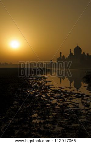 The beautiful view of Taj Mahal with reflection during sunrise from the Yamuna river Agra India.