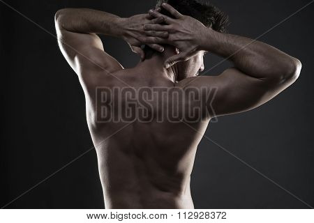 Handsome Muscular Bodybuilder Posing On Gray Background. Low Key Studio Shot