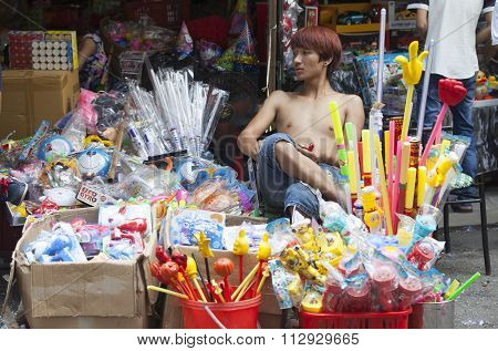 Young man selling colorful made in China toys