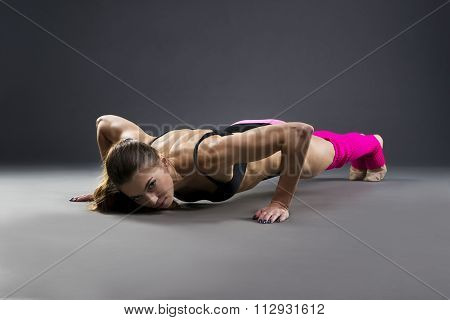 Beautiful Young Muscular Woman Doing Push Ups In Studio