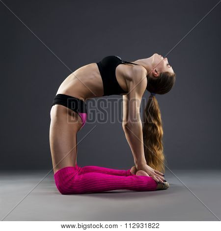 Muscular Attractive Fitness Woman Warming Up In The Studio On Gray Background