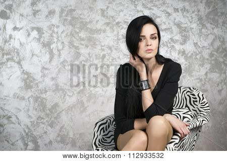 Beautiful Young Woman Sitting In A Armchair. Black Dress, Shoes And Stockings