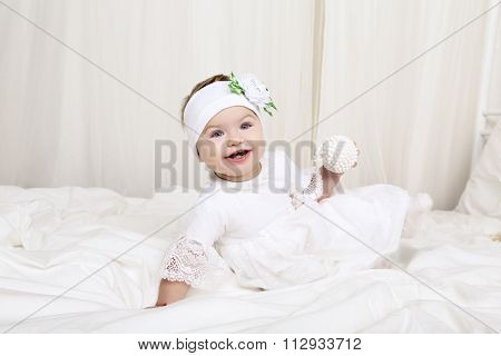 Cute Little Baby Girl In White Clothes, Sitting On Bed, Playing With Toy