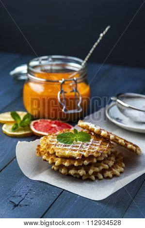 Wafers on baking paper with a jar of persimmon jam
