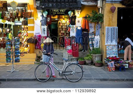 Woman with her bicycle in traditional conical hat on the market street of Hoi An, Vietnam