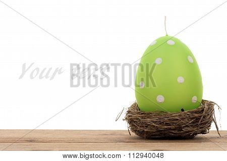 Easter decoration - green candle in the shape of egg and nest isolated.