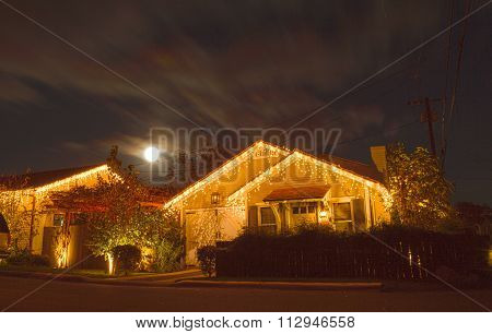 A full moon peaks over a home with Christmas lights