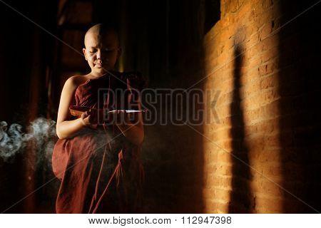 Young novice monk learning inside monastery.