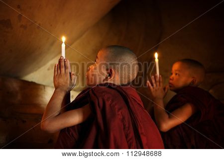 Little novice monks praying in front candlelight