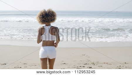 Athletic young african american woman running on the beach in slow motion