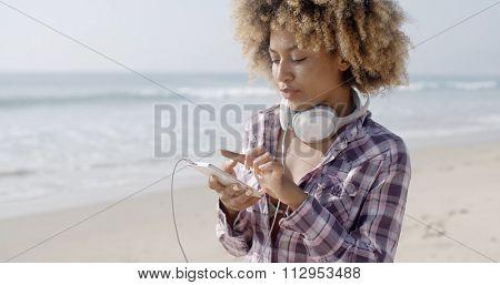 Beautiful girl listening to music on the beach