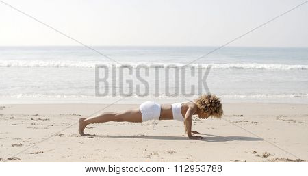 Fitness young woman doing push ups on beach with sea on the backgrond