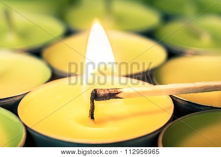 yellow burning candle with a lit matchstick