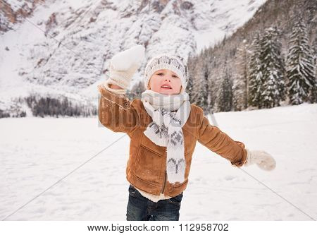 Child Throwing Snowball Outdoors Among Snow-capped Mountains