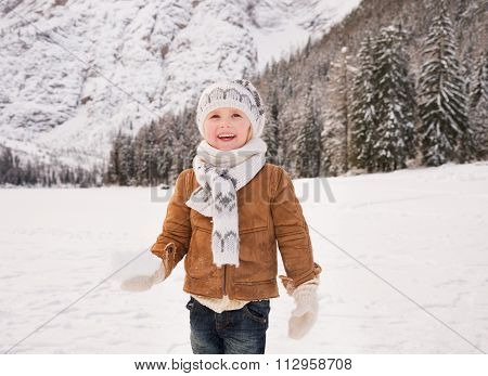 Child With Snowball Standing Among Snow-capped Mountains