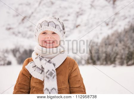 Portrait Of Child Standing Outdoors Among Snow-capped Mountains