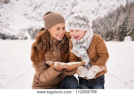 Happy Mother And Child Playing With The Snow In Winter Outdoors