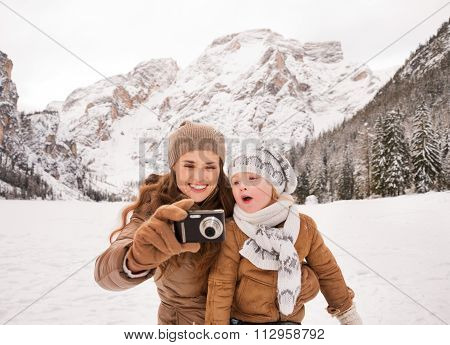 Mother And Surprised Child Checking Photos In Winter Outdoors