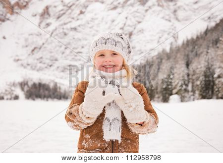 Child Showing Snowy Mittens Outdoors Among Snow-capped Mountains