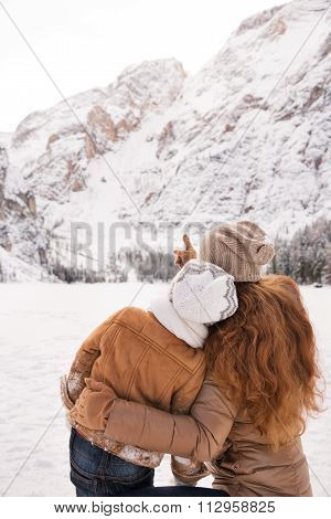 Seen From Behind Mother Pointing Child On Snow-capped Mountains
