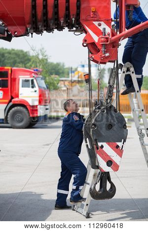 MOSCOW - MAY 29, 2015: Two firefighters near the truck with fire crane