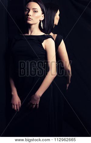 Woman With Dark Hair In Elegant Dress And Bijou, Posing Beside Mirror