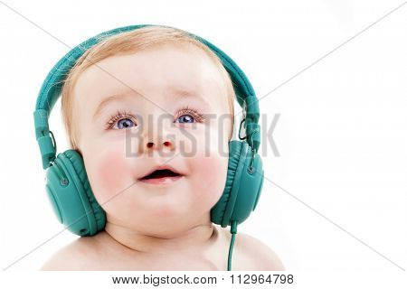 Smiling baby with headphones listening to music, isolated on white background