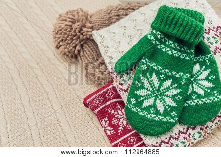 Green knit gloves on wooden background for winter image