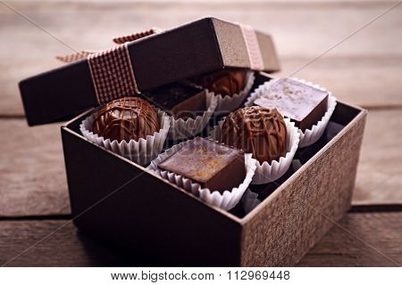 Delicious chocolate candies in beautiful gift box on wooden background