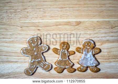 Happy Family Concept - Gingerbread Homemade Figures Of Mother, Father And Daughter Together On A Woo