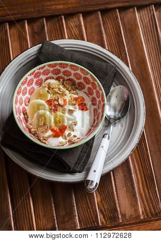 Natural Yoghurt With Banana, Dried Apricots And Crunchy Granola In A Vintage Bowl On A Dark Wooden T